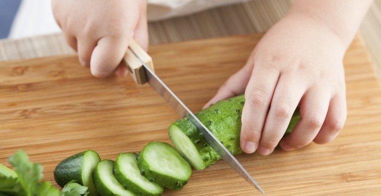 Mains d'enfant coupant un concombre
