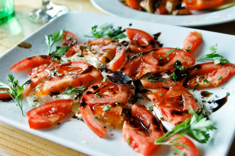 Tomatoes with fresh cheese and herbs eaten in Croatia.